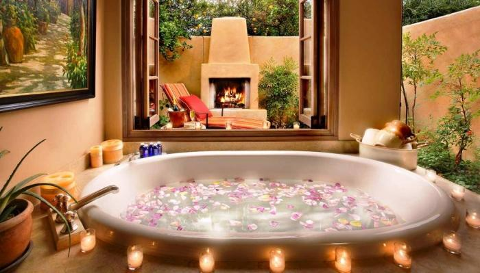 White Oval Bathtub With Candles Connected To Outdoors